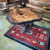 Rustic live edge table on red southwest rug.