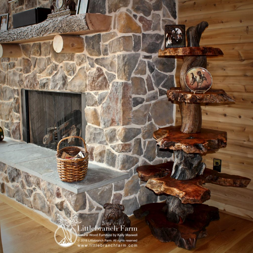 Rustic natural wood furniture next to stone fireplace.