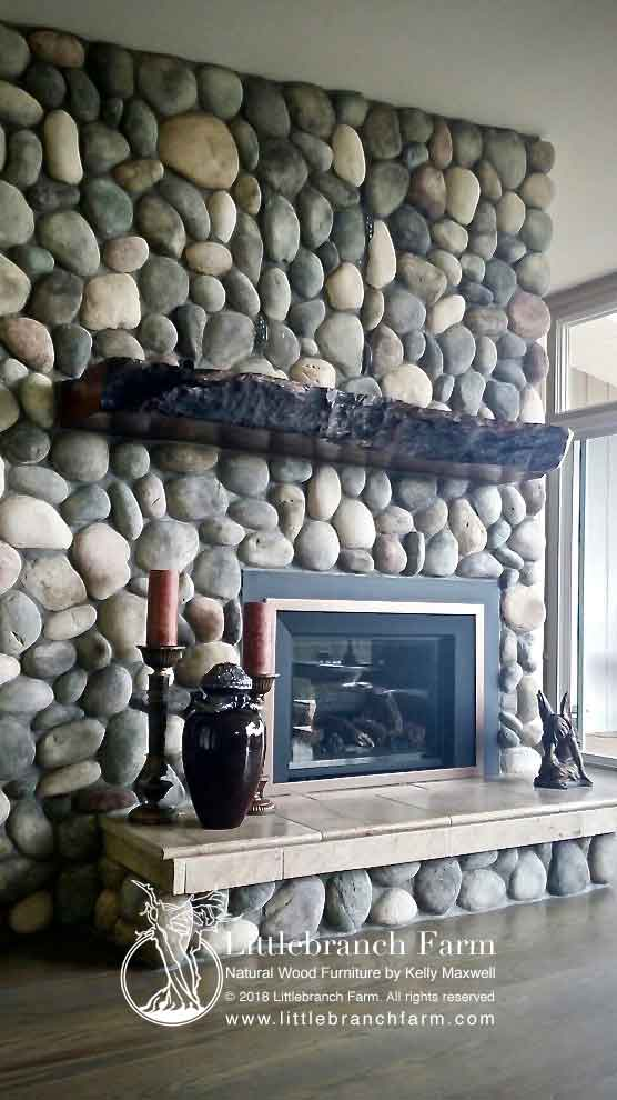 River stone fireplace with live edge wood.