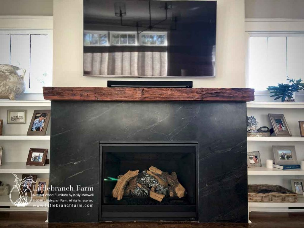 Rustic Redwood mantel on black fireplace