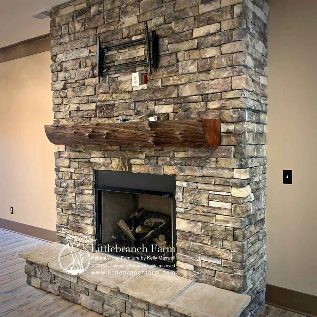 Stacked stone fireplace with rustic mantel.