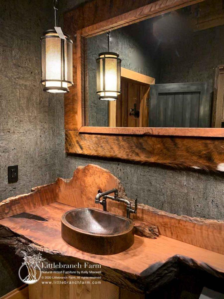 Rustic bathroom vanity with cowhide mirror.